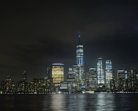 Shot of Manhattan at night pcutred from New Jersey, with blue beams representing the WTC Twin Towers