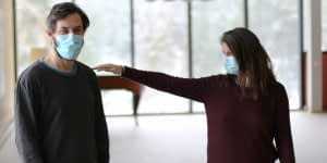 A couple with masks measuring the distance between themselves