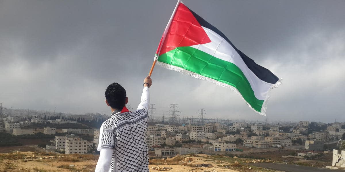 Young man with Palestinian flag overlooking Gaza
