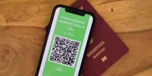 Mobile phone with COVID passport screen and paper passport