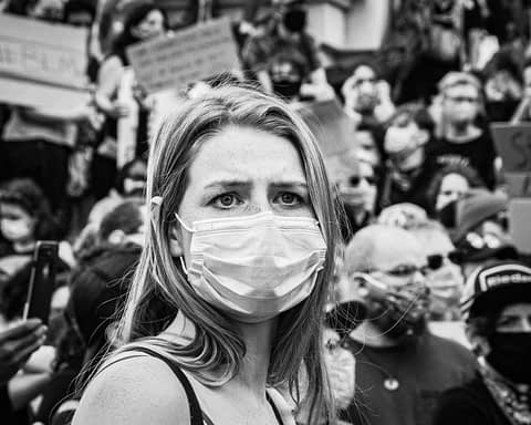 Protesters with a woman in a mask in front
